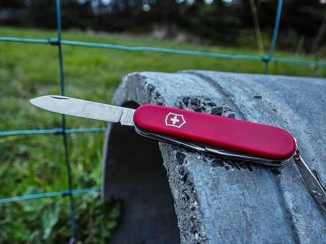 Victorinox CLIMBER en rojo abierta por cuchilla grande sobre tubo de cemento