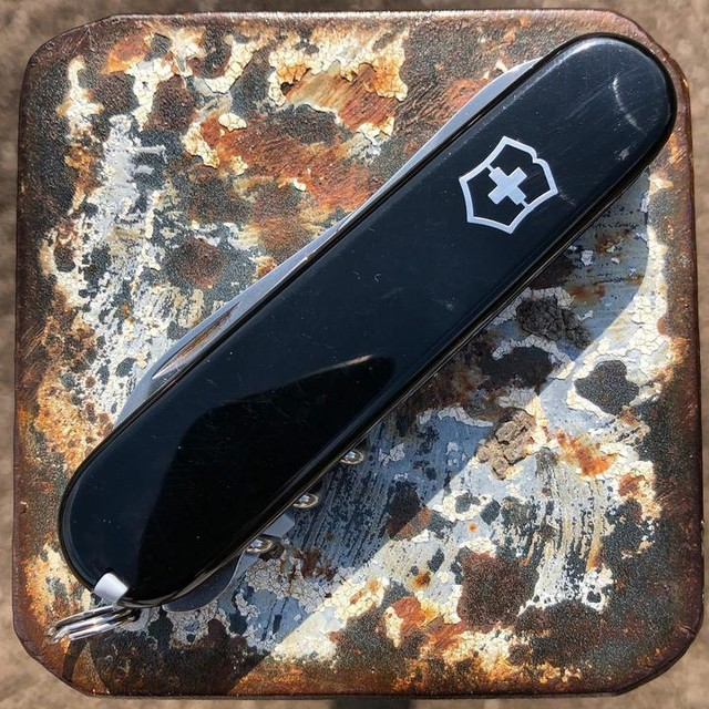 navaja suiza en negro sobre chapa oxidada