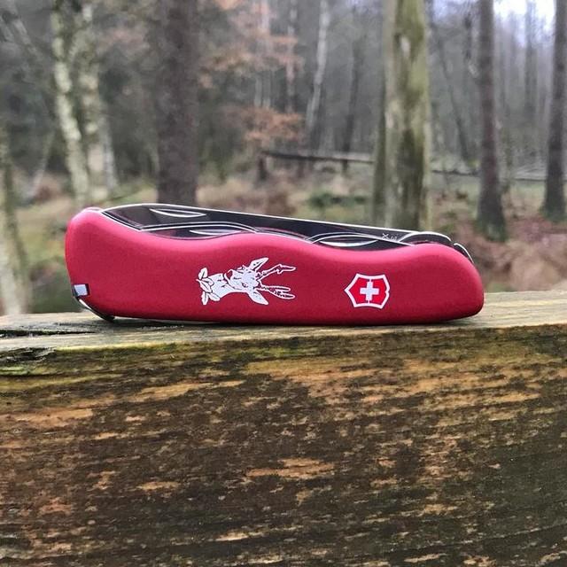Navaja suiza con cachas rojas sobre tronco de madera
